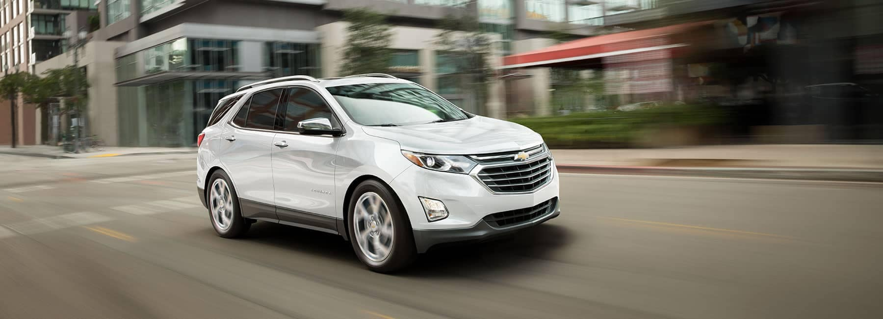 White 2019 Chevrolet Equinox Driving on City Street Angled View