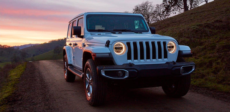 Light Blue Jeep Wrangler on Dirt Road