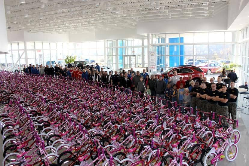 hundreds of bikes with people standing in front of them