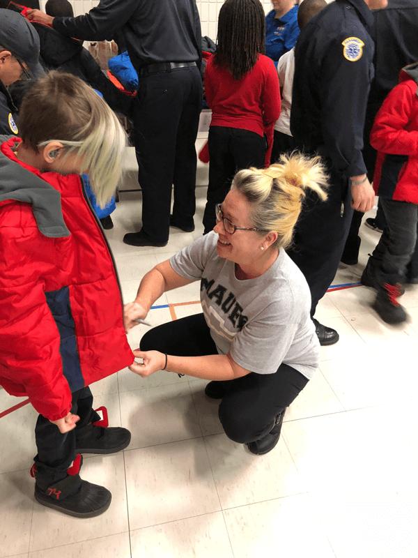 Volunteer zipping up coat on child