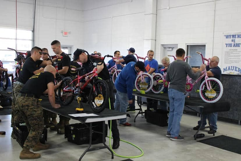 marines and volunteers working on bicycles