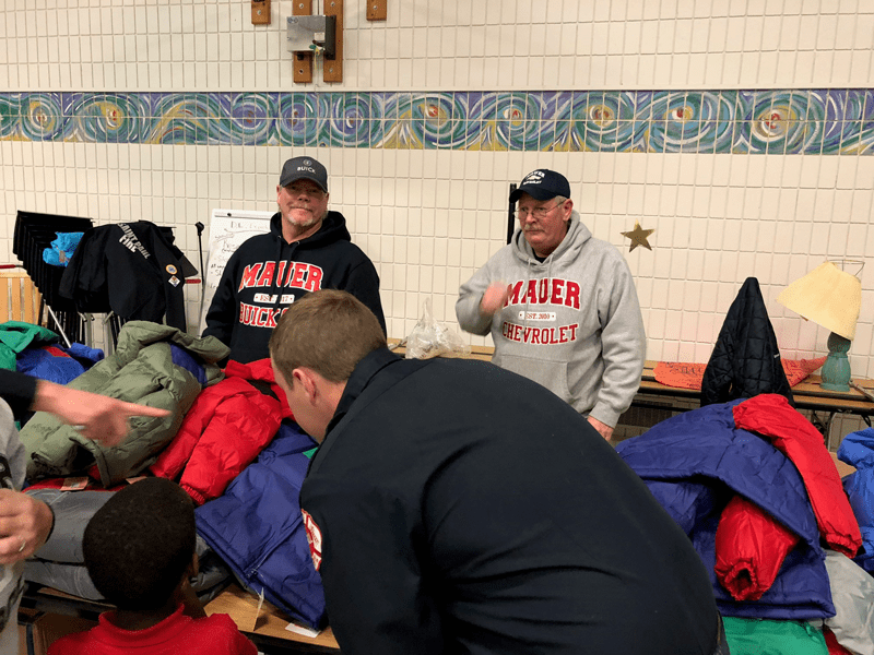 Volunteers standing by coats on table