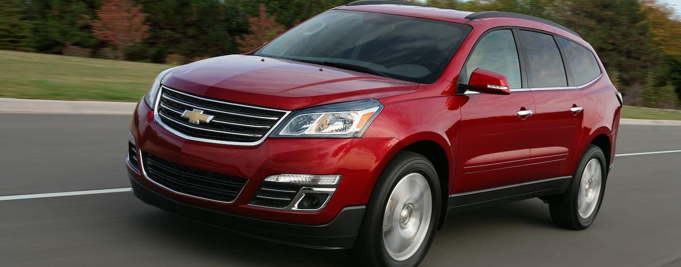 A red 2016 Chevy Traverse LTZ, a popular used car in Cincinnati, is driving on a rural road.
