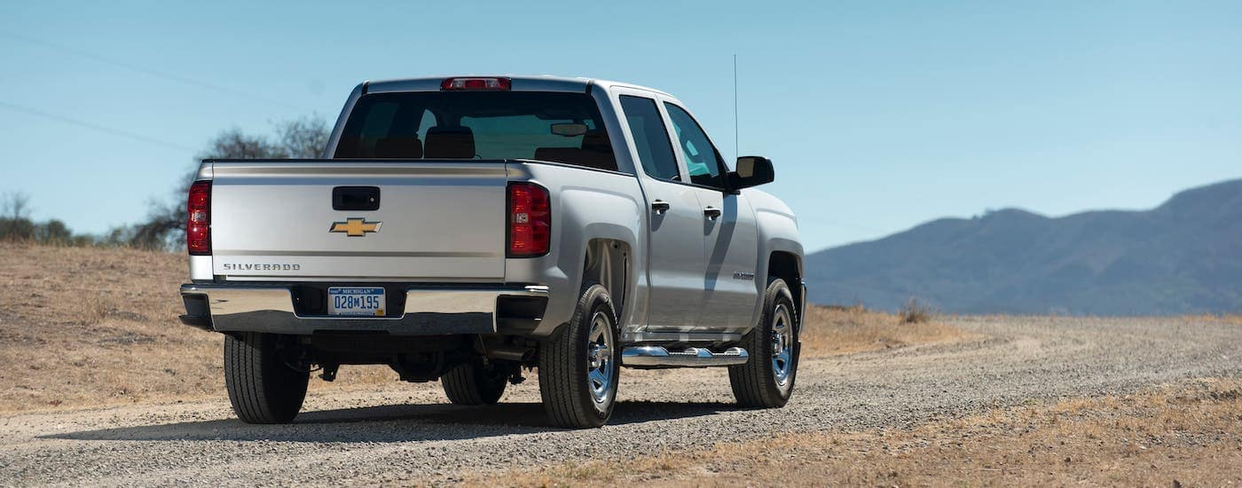 A silver 2018 Chevy Silverado is facing away and overlooking a dirt road and distant mountains.