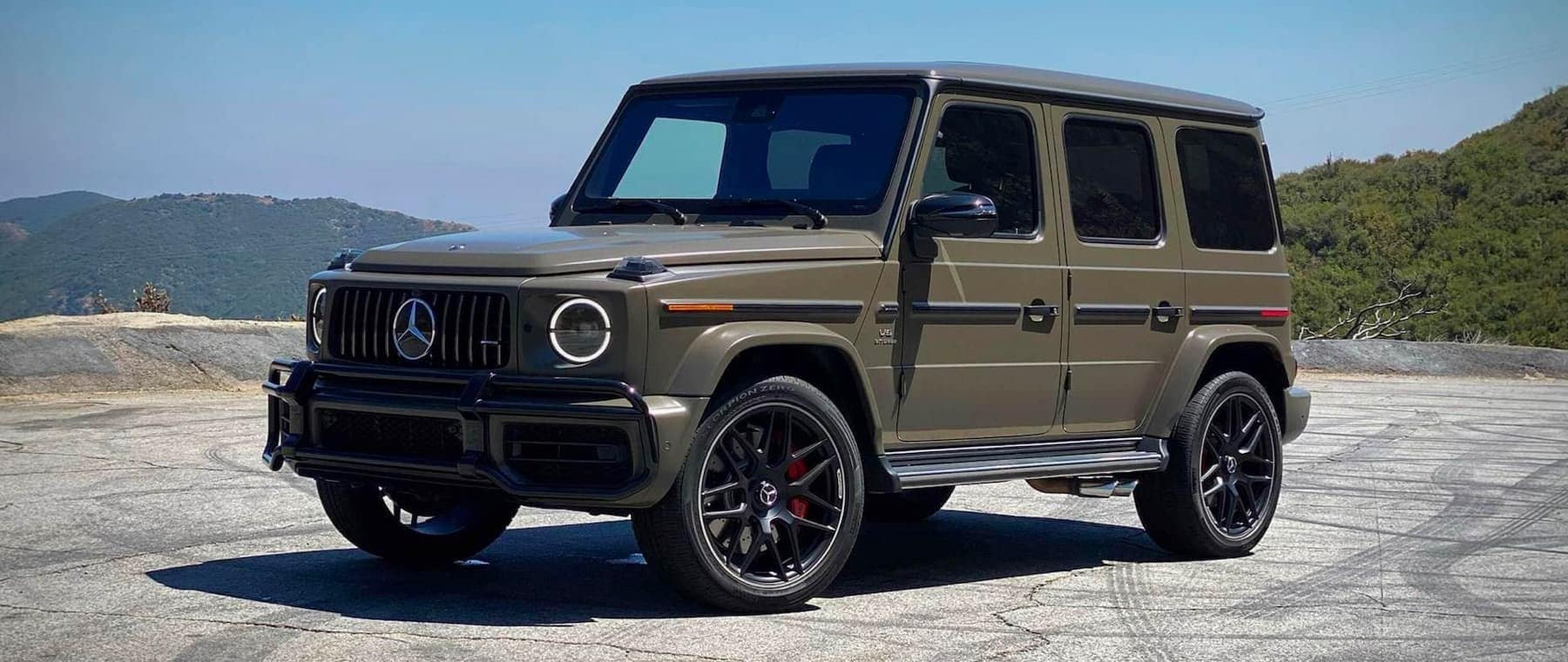 Green Mercedes-Benz G-Wagon on concrete with brushy hills in the background