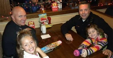 children sitting in restaurant booths with police officers