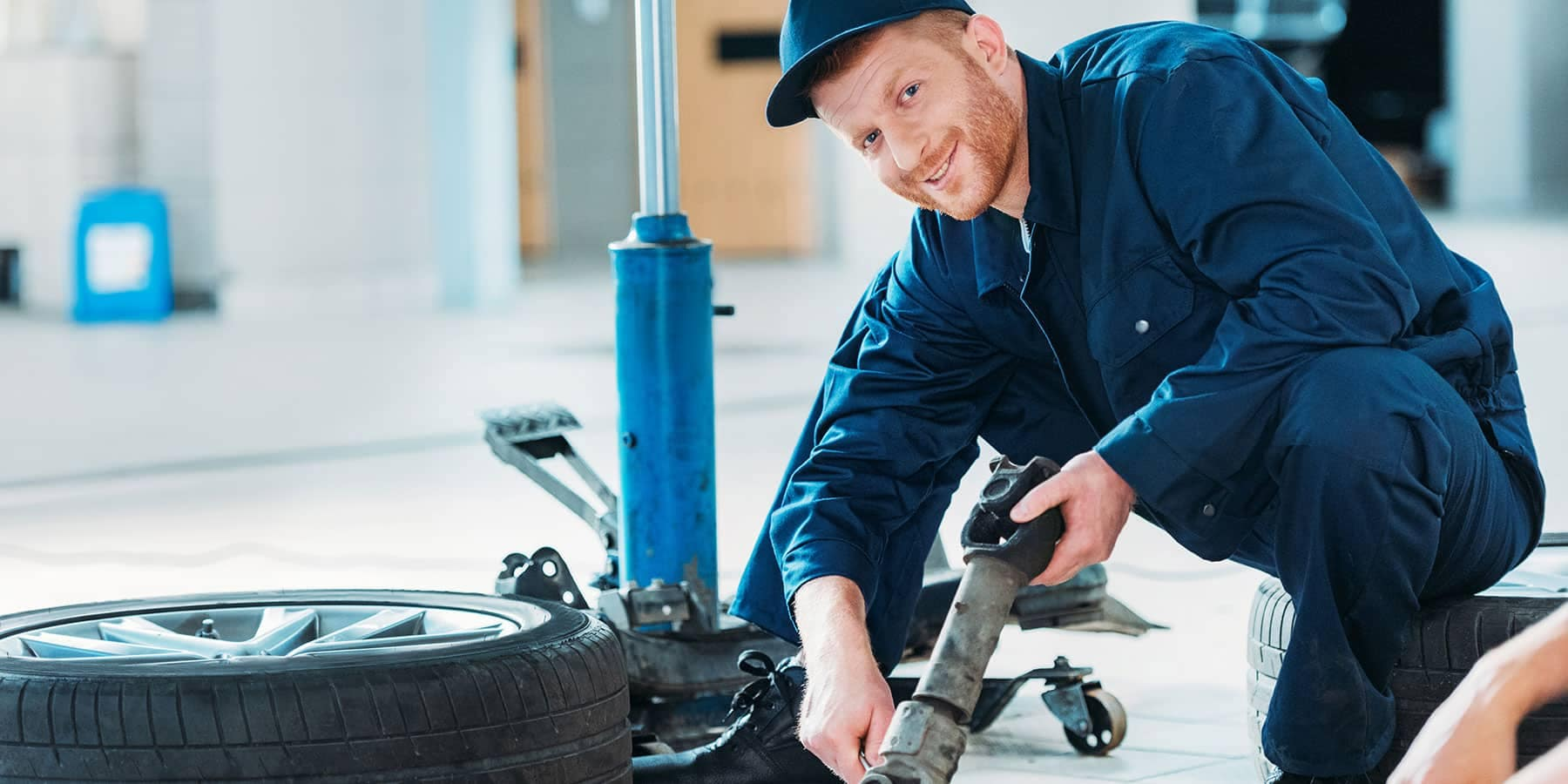 picture of mechanic working on a car smiling