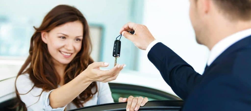 car dealer giving car key to smiling customer