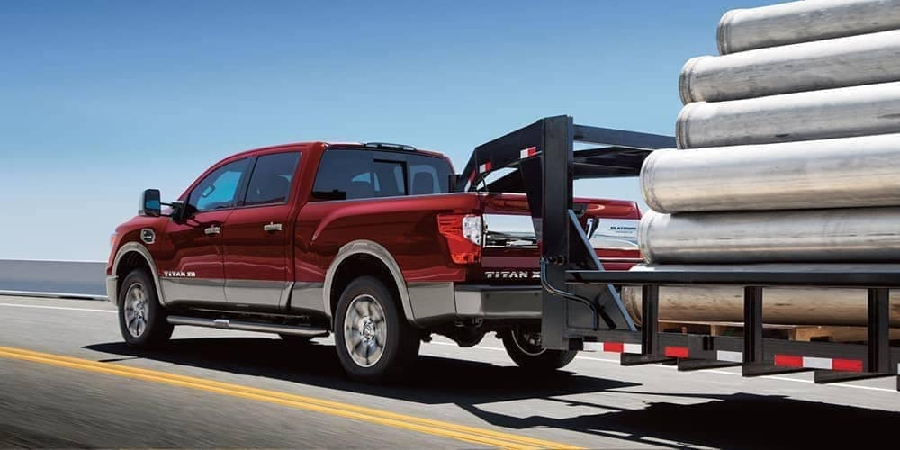 2019 Nissan Titan towing a trailer of large pipes