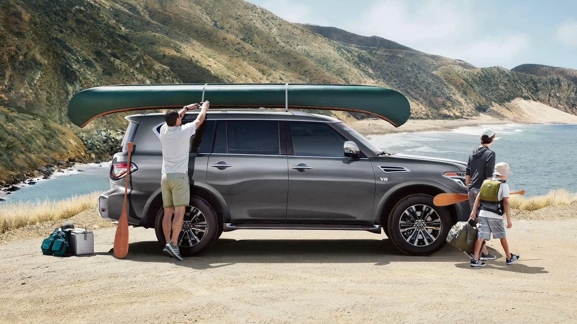 2020 Nissan Armada with canoe on top getting unloaded by a coastline