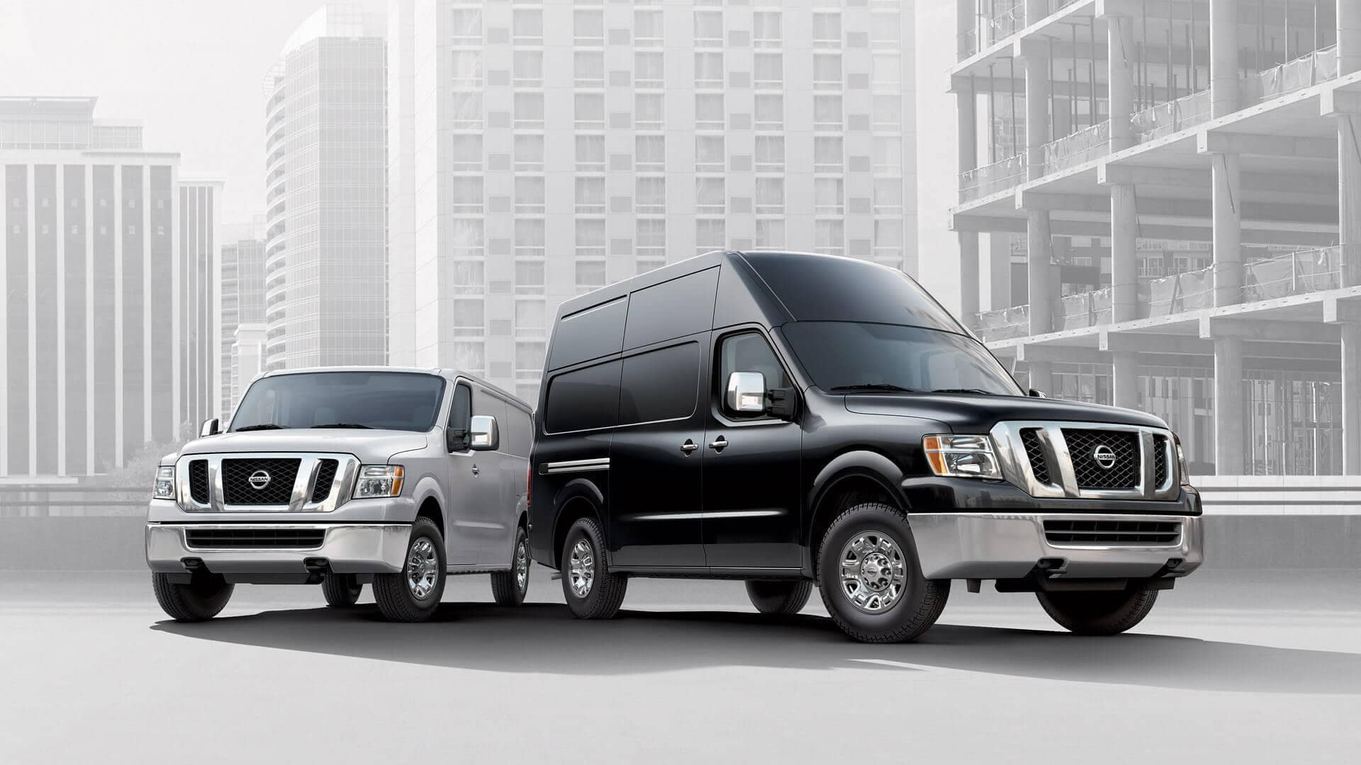 2020 Nissan NV Cargos with buildings undergoing construction behind them