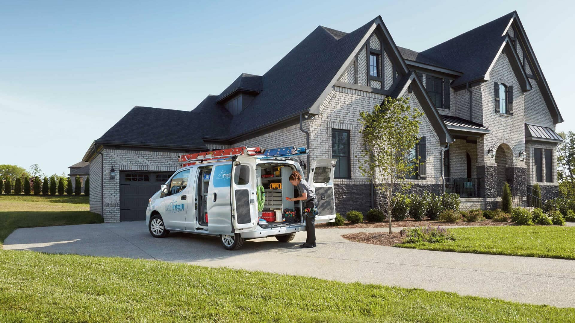 2020 Nissan NV200 Compact Commercial parked in a house driveway with worker getting tools out of the back