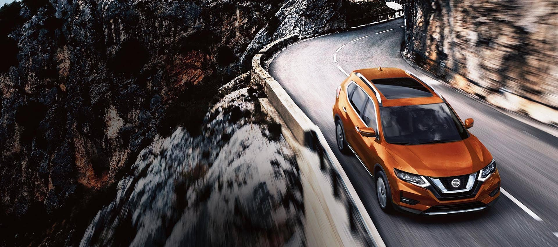 2020 Nissan Rogue driving alongside a mountain cliff