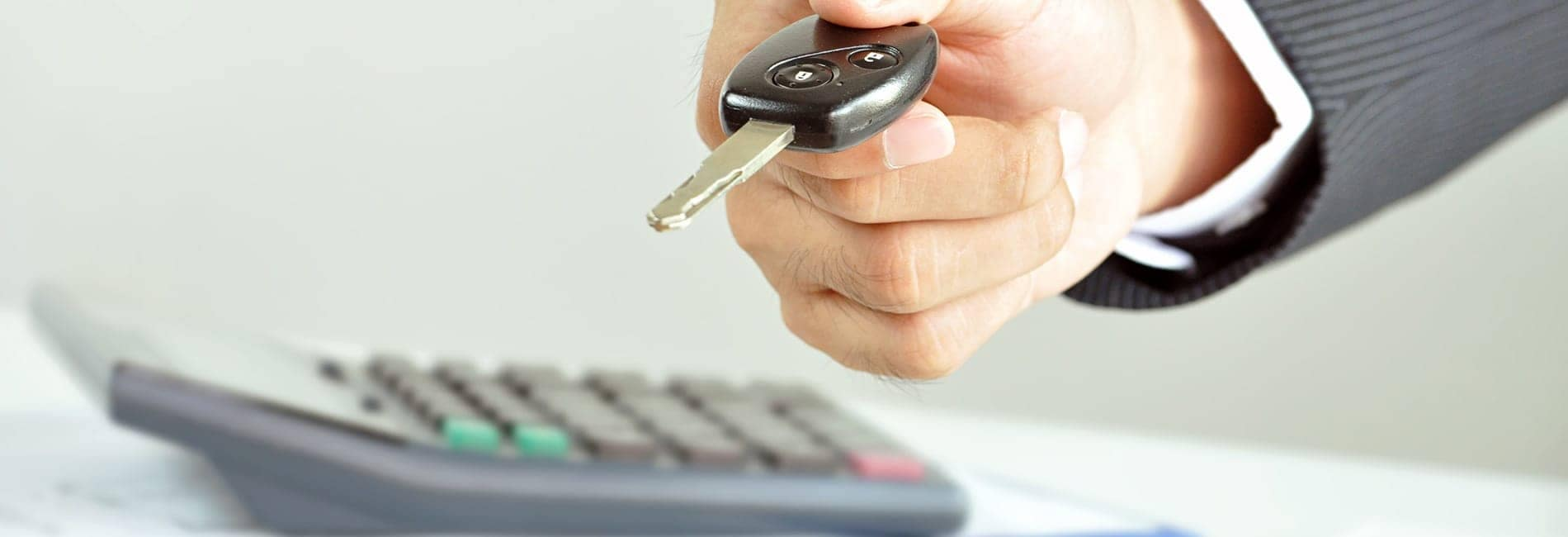 man holding key next to calculator