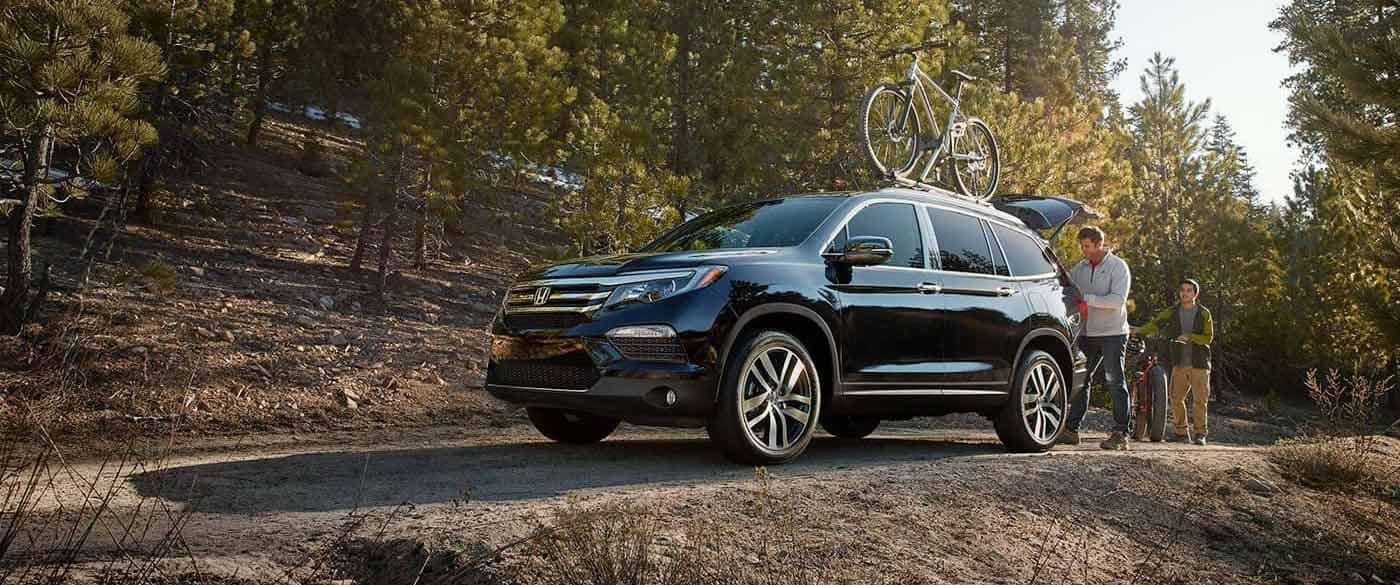 2018 Honda Pilot parked at bike trail with bikes on roof rails