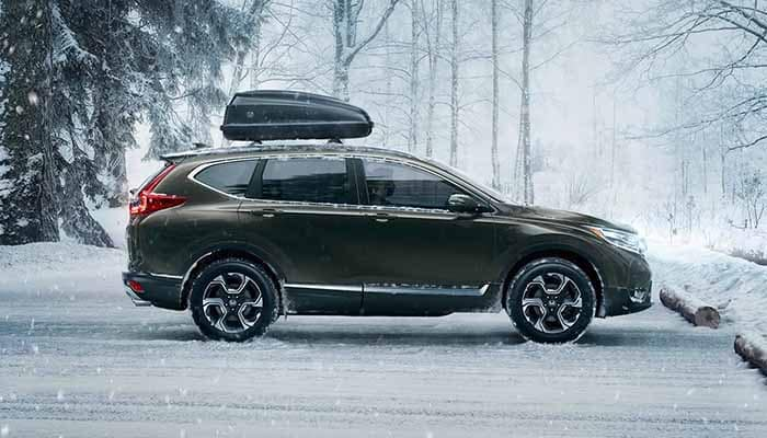Honda CR-V parked in the snow with cargo container on roof rails
