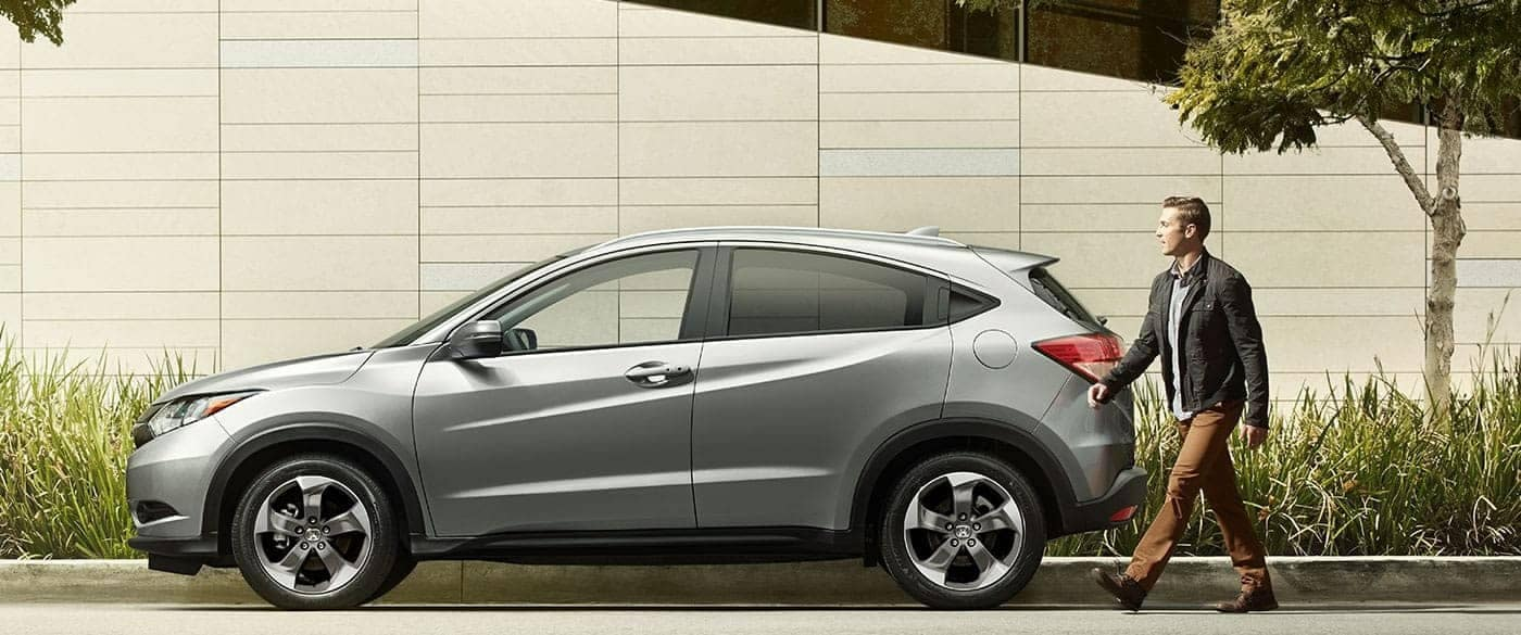 Man walking to his 2018 Honda HR-V parked on side of the road