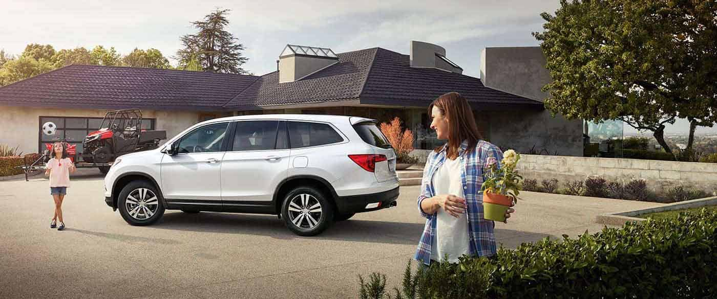 2018 Honda Pilot parked outside a home with a trailer