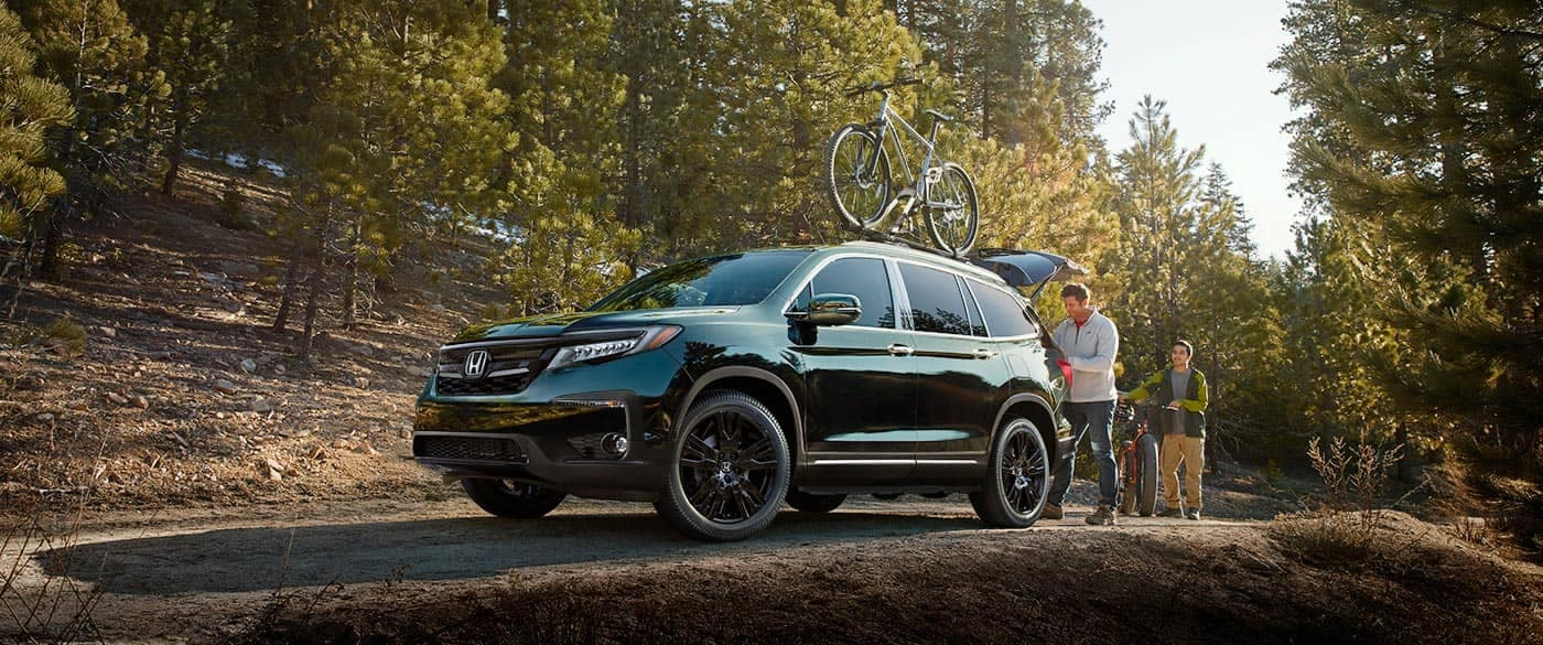 2018 Honda Pilot parked at trails with bikes on roof rails