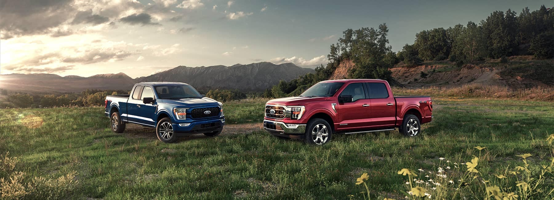 Two 2021 Ford F150 trucks in a mountain valley