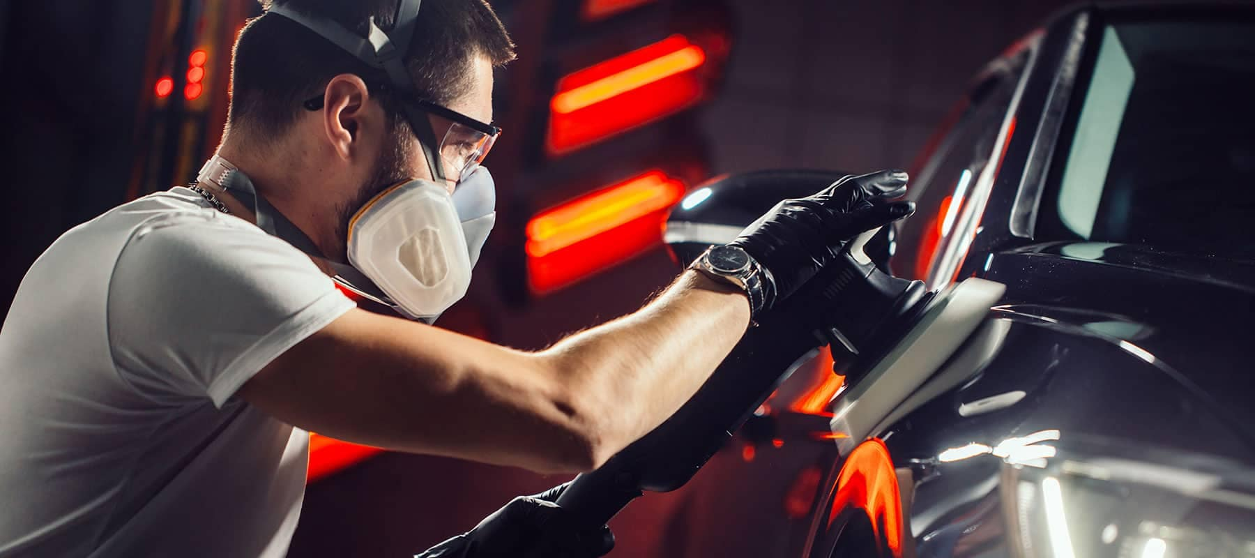 Man buffing a car with a respirator on
