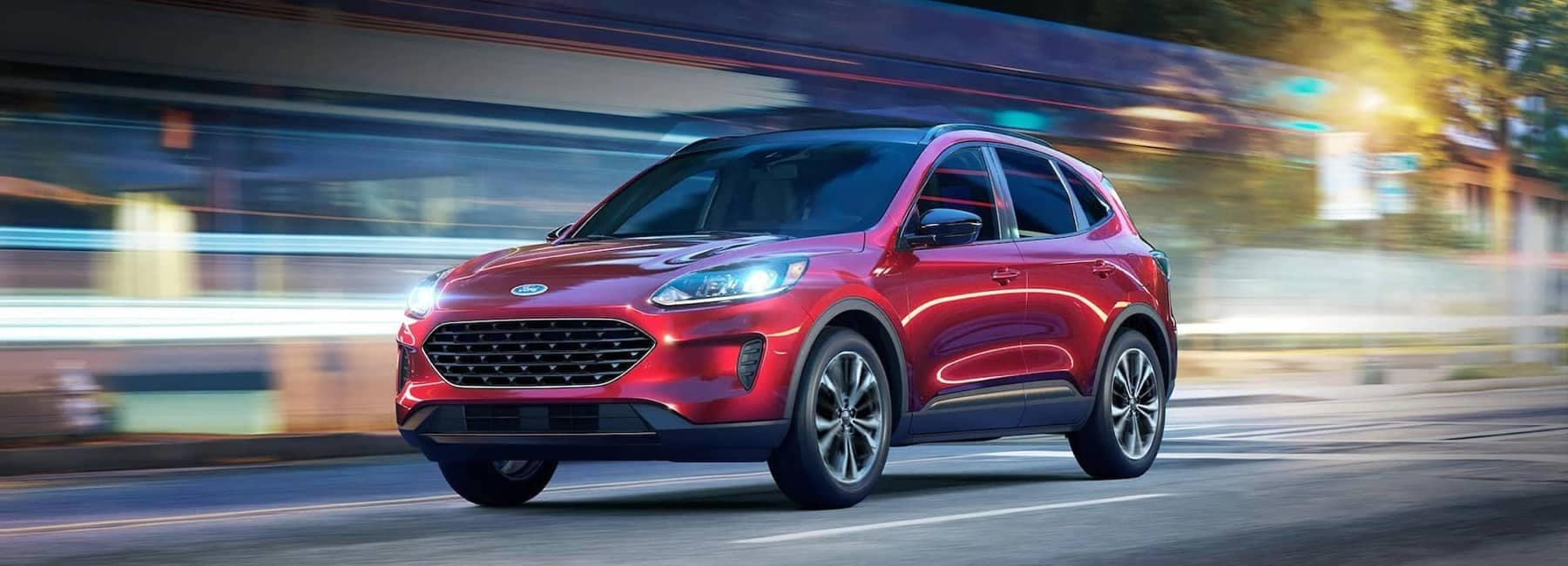 2021 Red Ford Escape driving through a city at night-1800x650