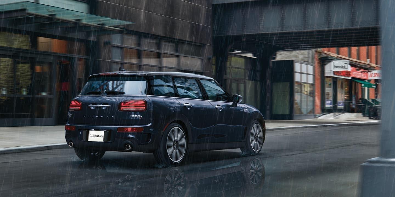 Blue MINI Clubman driving through a rainy city