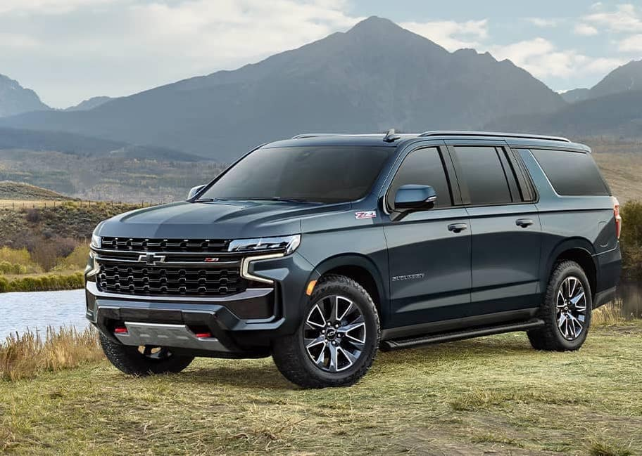 A blue 2021 Chevrolet Suburban parked in front of picturesque mountains copy