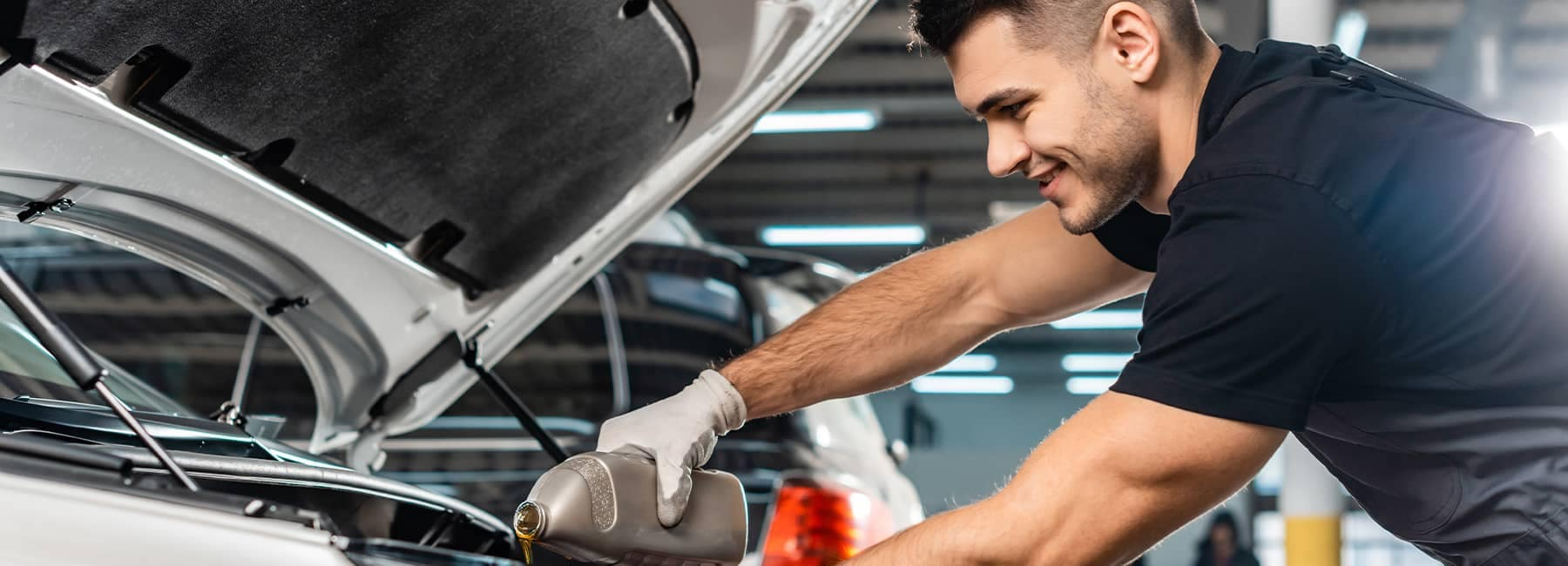 Mechanic replacing engine oil in a vehicle