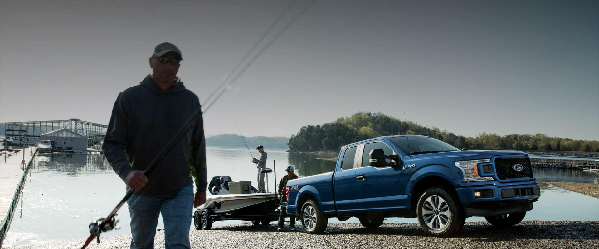 Three men are taking their blue Ford pick-up truck to go on a fishing trip