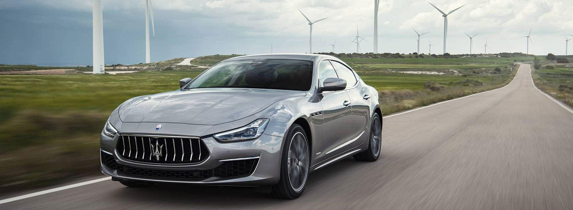 Silver Maserati Ghibli driving down a road with windmills in the background