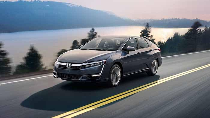 2018 Honda Clarity Plug In Hybrid driving down the road in front of a lake and forest