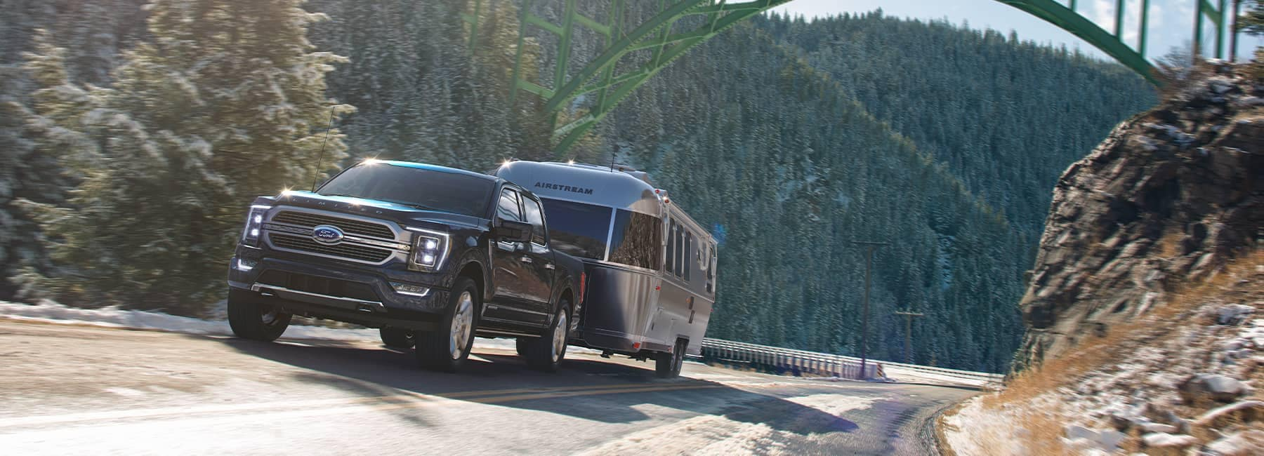 A black Ford F150 hauling a silver Airstream RV through a mountain pass