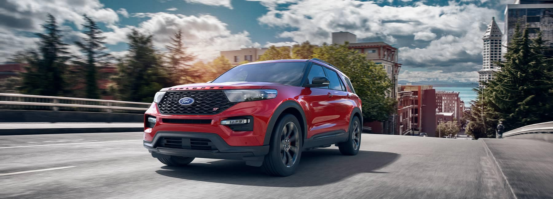 Red 2021 Ford Explorer driving up a hill out of a city