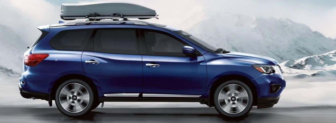 A blue 2019 Nissan Pathfinder is shown from the side on a snowy road.