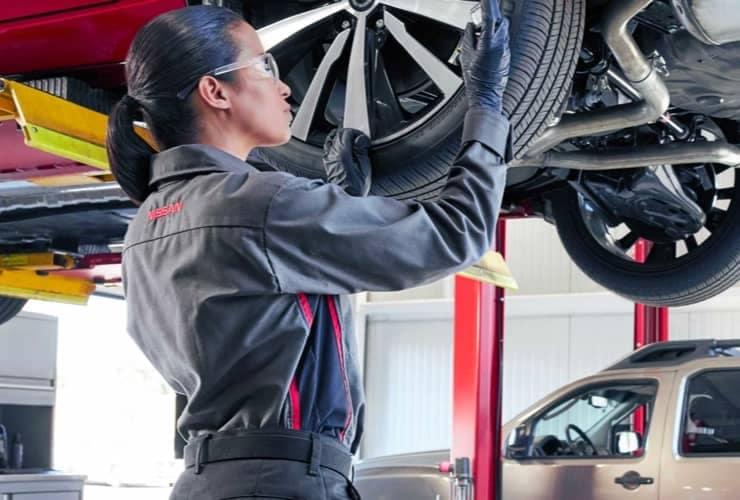 Nissan service tech checking tire
