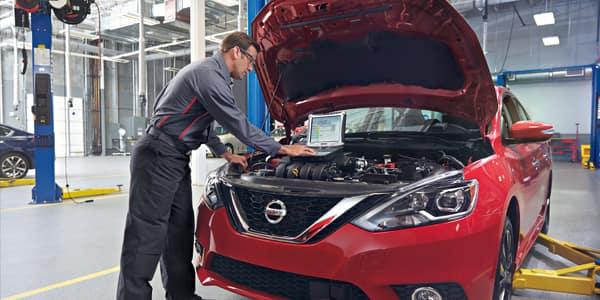 Mechanic servicing a red Nissan car