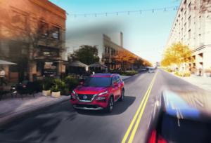 2021 Nissan Rogue Driving in Scarlett Ember