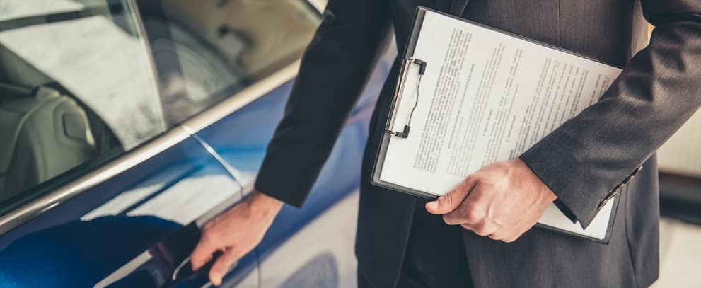 Sales Person Holding Car Loan Application