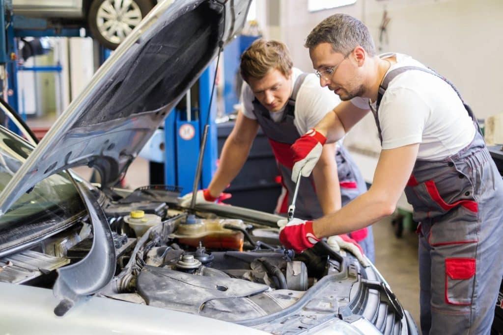 Two Mechanics Fixing Vehicle