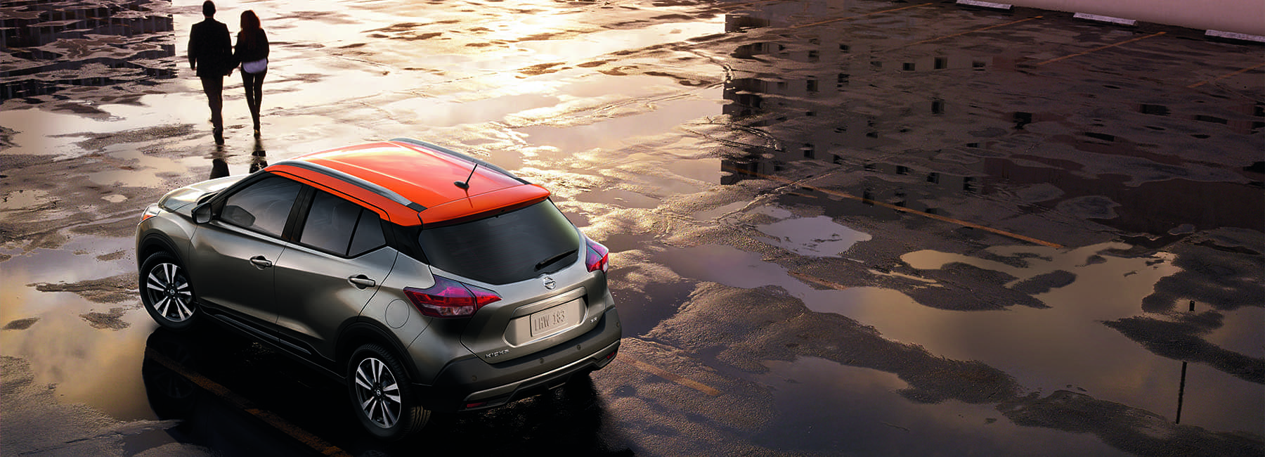 couple walks away from 2020 Nissan Kicks on wet pavement