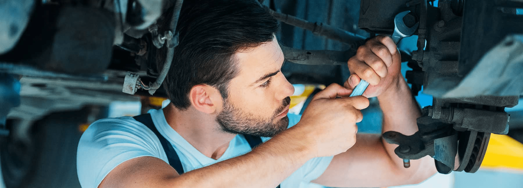service man with wrench loosens bolt under car