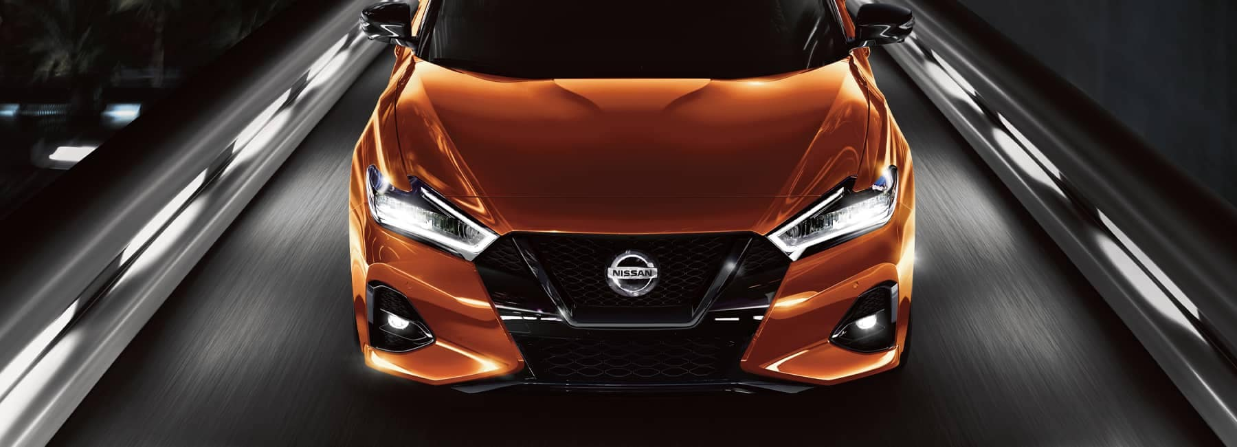 Front angle shot of a 2021 orange Nissan Maxima at night