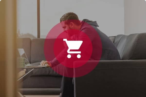 person sitting on a couch with a shopping cart icon