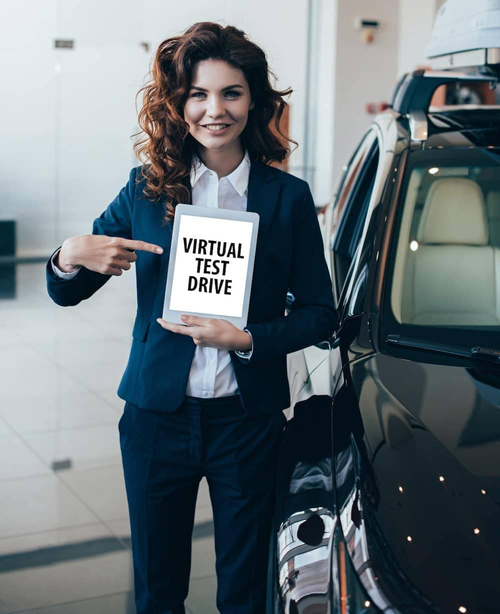 A woman holding a virtual test drive sign