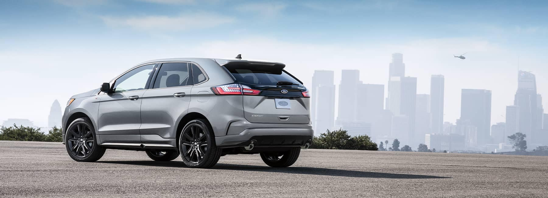 A silver 2021 Ford Edge parked with a cityscape in the background