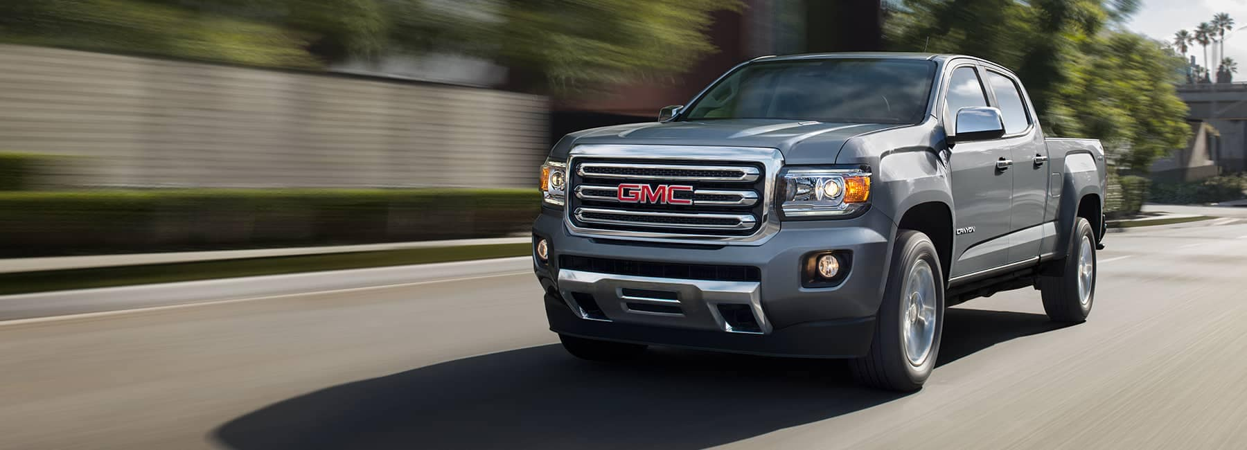 Grey 2020 GMC Canyon driving down a city street