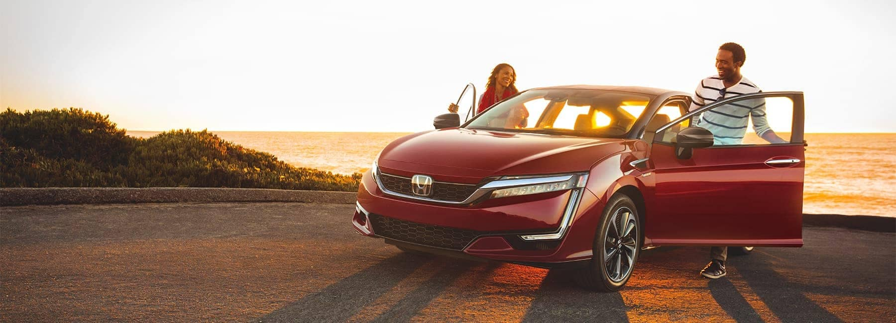 Happy Couple getting into a 2020 Red Honda Clarity