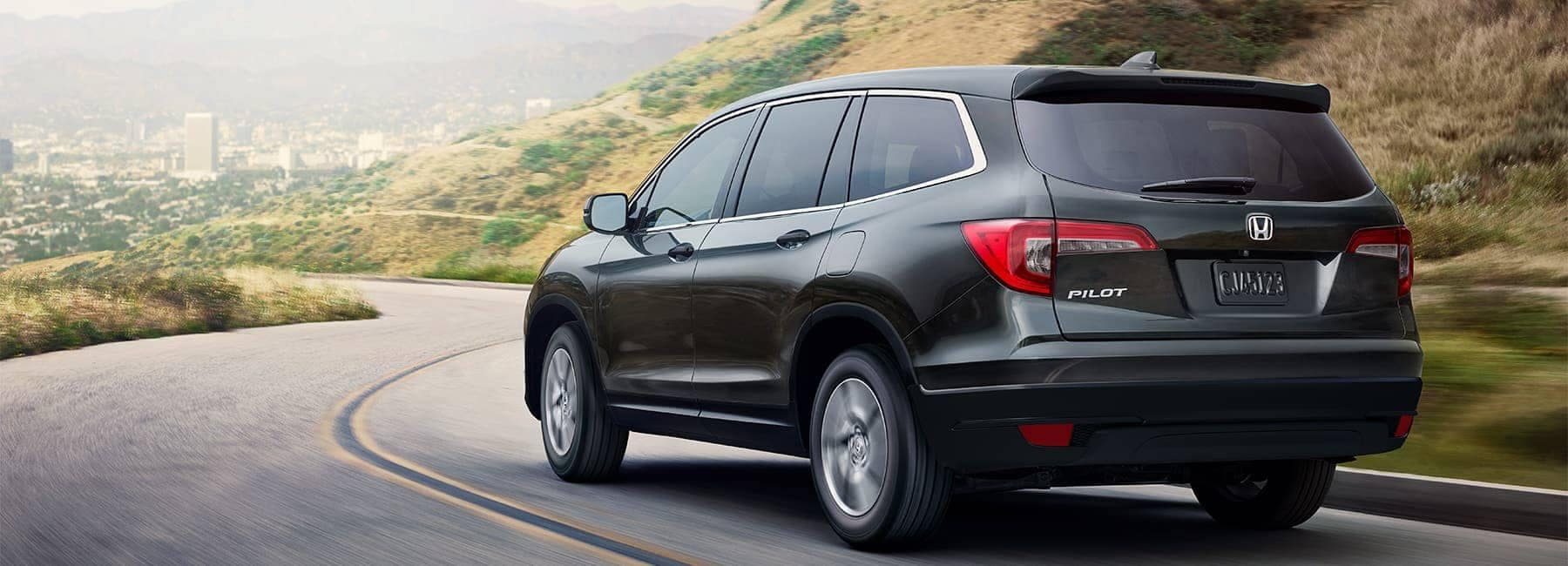 2021 Black Honda Pilot LX driving on a curved road
