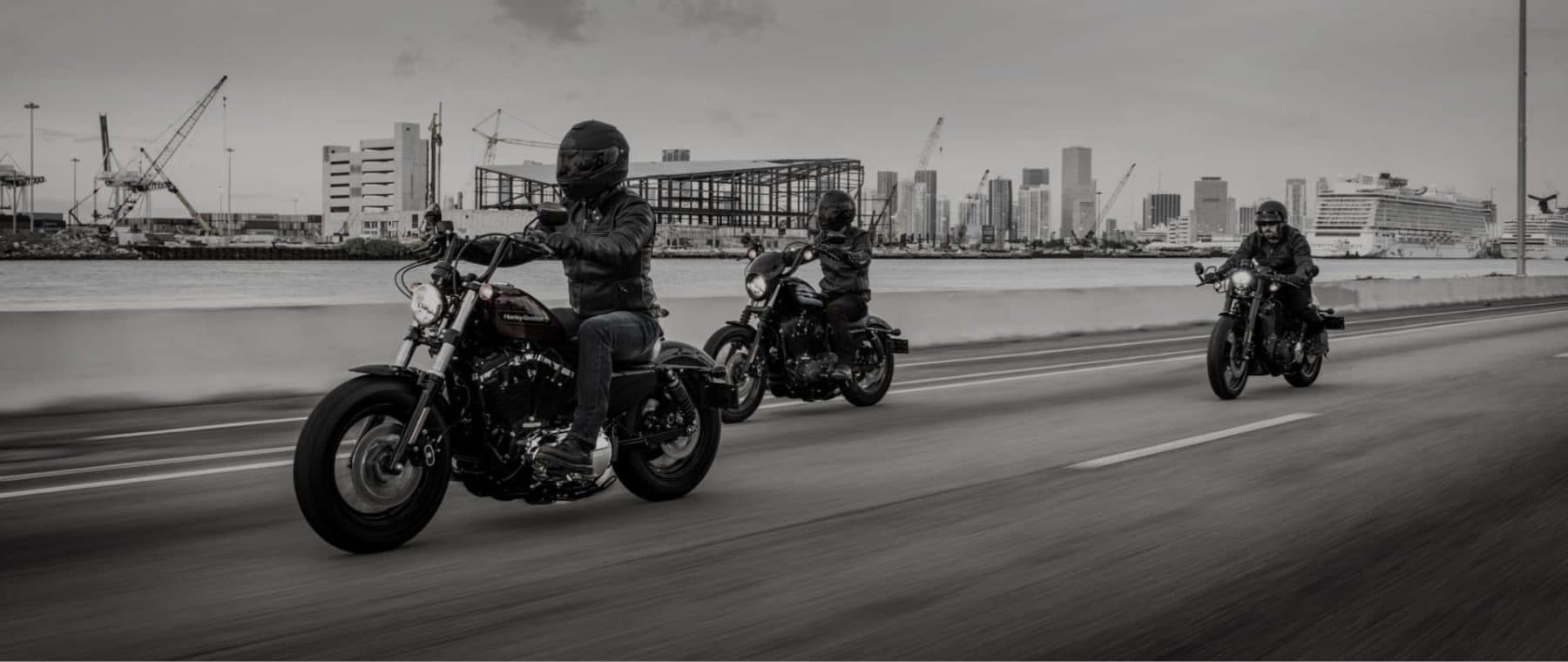 Three motorcyclists riding past a dockside in grayscale